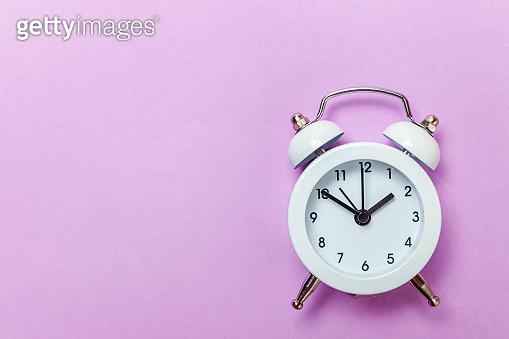 Vintage alarm clock Isolated on purple violet pastel background