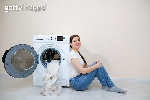 woman sitting near washing machine with clean laundry