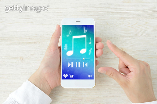 Human Hands making use of music application with smart phone