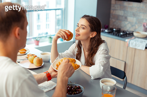 Dark-haired husband giving croissants for wife eating apple