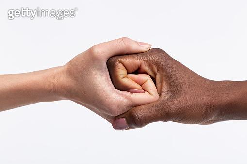 Women with white skin shaking hand of her dark-skinned friend