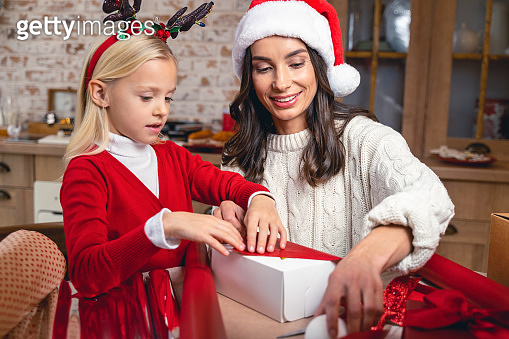 Girl and a woman wrapping a Christmas gift