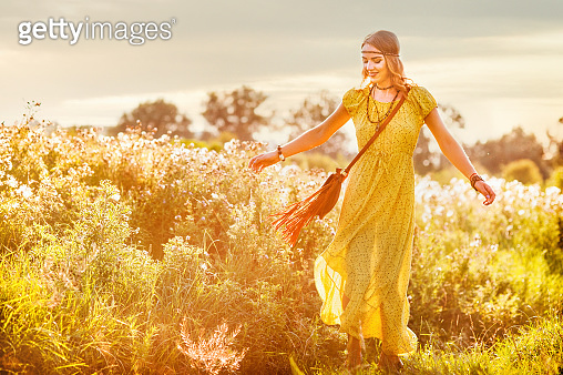 Smiling bohemian girl in yellow dress with guitar dance on the field at sunset warm light