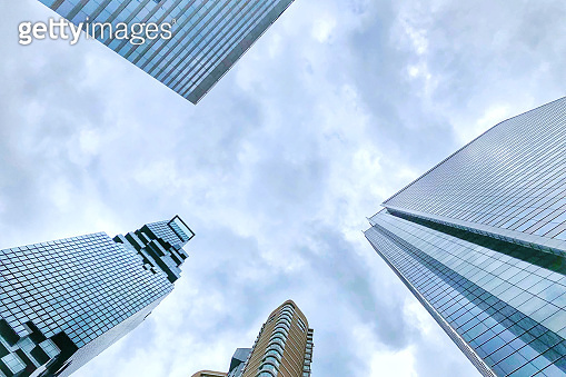 Perspective of tall skyscrapers, Modern glass silhouettes of office buildings in the city,Contemporary architecture stretch up to the blue sky in the financial district in downtown of Bangkok Thailand