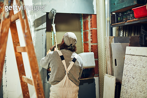 Painter painting walls with a extender roller indoors.