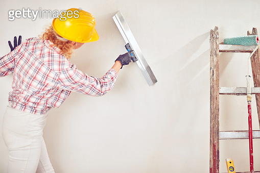Working woman plastering / painting walls inside the house.
