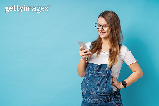 Smiling pregnant woman, with glasses, holding a mobile phone in one hand over blue background.