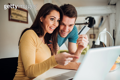 Couple using laptop and credit card