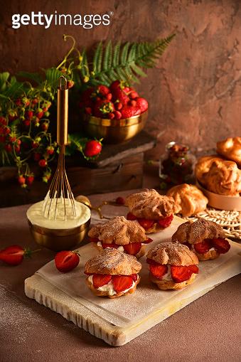 Eclairs custard cakes (shu, profiteroles) with strawberries on a dark background. Still life.