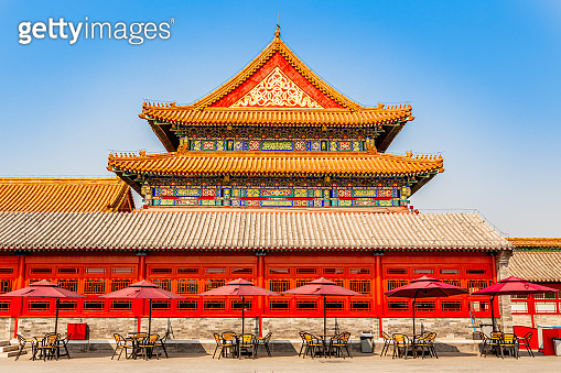 Summer cafe with tables and umbrellas at the wall of one of the royal emperor palace in Forbidden city, Beijing, China