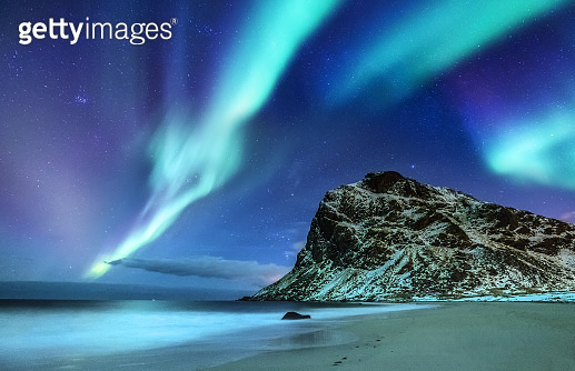 Aurora borealis on the Lofoten islands, Norway. Green northern lights above mountains and ocean shore. Night winter landscape with aurora and reflection on the water surface. Natural background in the Norway