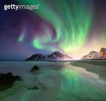 Aurora borealis on the Lofoten islands, Norway. Green northern lights above mountains and beach. Night sky with polar lights. Night winter landscape with aurora. Natural background in the Norway