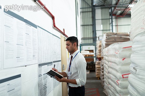 Male supervisor writing on a diary in warehouse