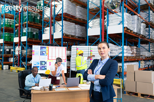 Female manager standing with arms crossed in warehouse