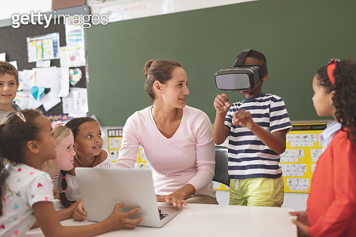 Schoolboy using virtual reality headset at school in classroom
