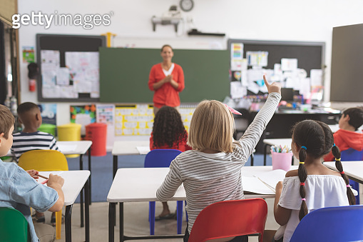 Caucasian schoolgirl raising hand in classroom at school