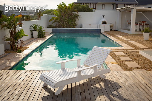 Empty wooden sun lounger near swimming pool in backyard