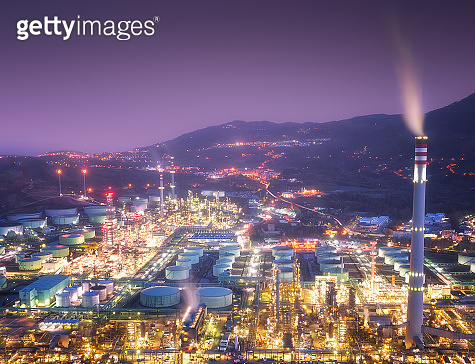 industrial factory with smokestacks and smoke at night