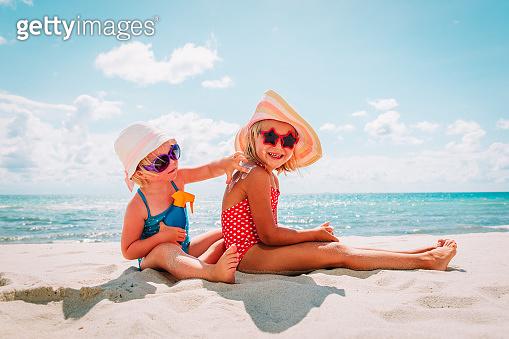 sun protection, cute girls with sun cream at beach