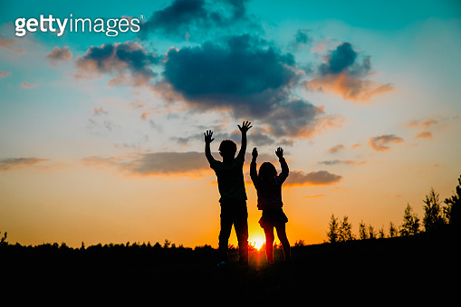 silhouette of happy boy and girl enjoy sunset nature