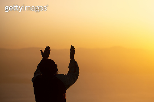 Young man praying in the morning, Hands folded in prayer concept for faith, spirituality and religion
