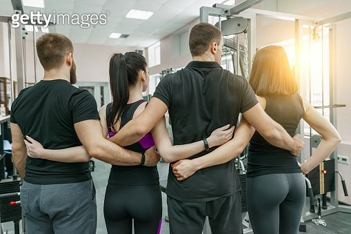 Group of young sports people embracing together in fitness gym backs. Fitness, sport, teamwork, motivation, people, healthy lifestyle concept