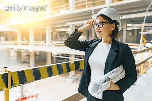 Portrait of adult female builder, engineer, architect, inspector, manager at construction site. Woman with plan, looking at building