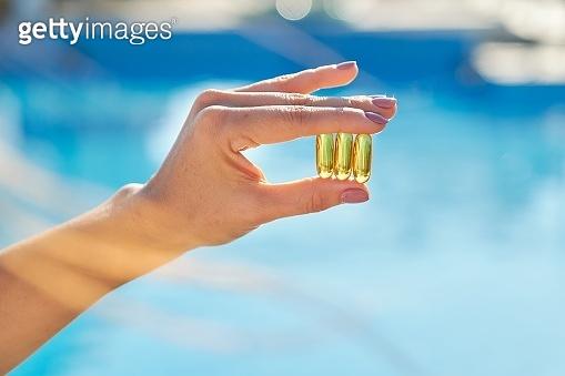 Vitamin D, E, A fish oil capsules cod liver oil omega 3 in female hand