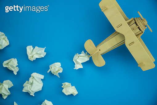 Wood Airplane with paper ball Instead of white clouds on blue paper background ,Preparation for Traveling and tour concept