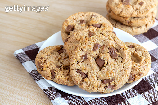 Chocolate chip cookies on a white plate on wood table.
