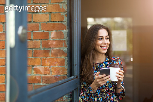 Young woman standing in front of coffee shop