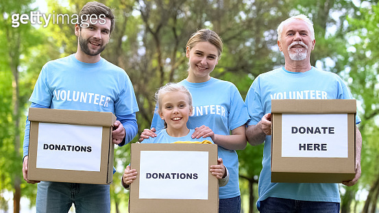 Smiling volunteers holding donation boxes looking camera, charity project, help