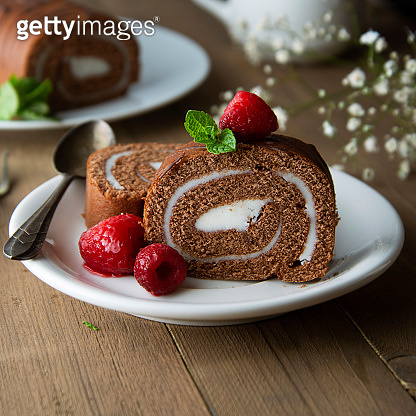 Delicious chocolate roll sponge cake with vanilla cream and mint leaves. Desert sweet food.