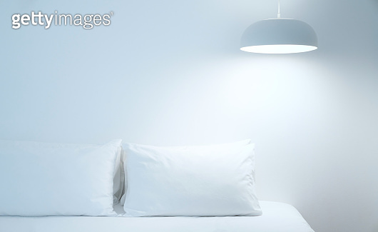 White bed sheets and pillows. Comfortable soft pillows on the bed. Close-up white bedding sheets and pillow on light wall room background. Fresh bed concept