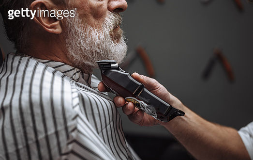 Hairdresser doing styling with the electric shaver for old man at barber shop