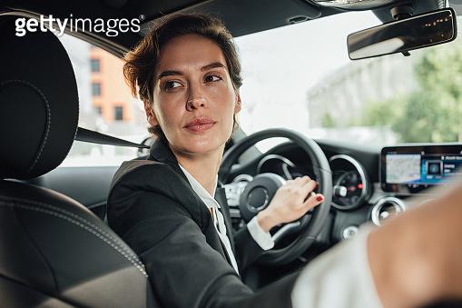 Portrait of caucasian businesswoman driving a car in reverse looking on back window