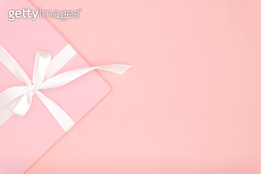 Pink gift or present box flat lay composition for Valentine day or women day, greeting card birthday with copy space on coral background. Concept holiday decoration top view for Christmas, love day