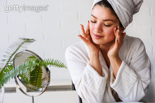 Portrait of young woman wearing bathrobe after skin care routine at home