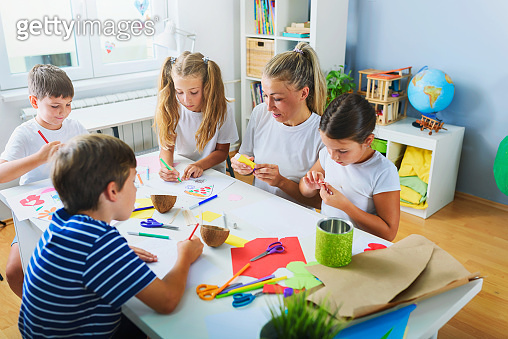Mother or school teacher with children. Creative arts and crafts project at school or at home.
