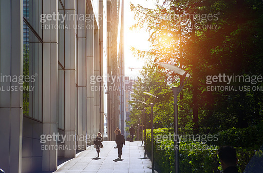 Canary Wharf at sunrise and people going to work in early morning. London, UK