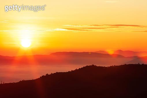 Glowing sunrise shines over mountain range.