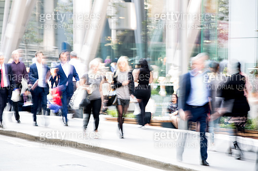 Blur of group business people walking in the City of London at lunch time next to the Lloyds bank. London. UK