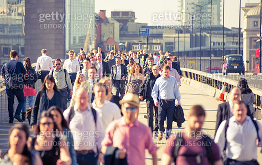 Business people and office workers crossing the London bridge on the way to work.  City of London busy business life. London, UK