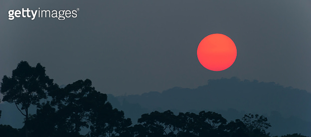 Gorgeous the red sun setting above the deep jungle and mountain range.