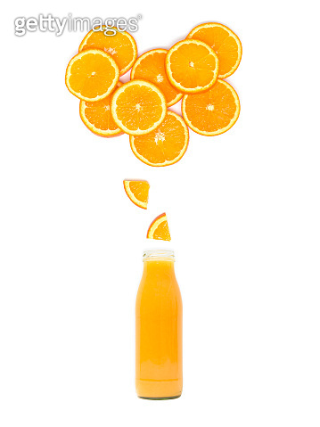 bottle with fresh orange juice is standing under many orange slices on white background