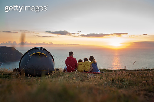 Beautiful family, camping on a hill, enjoying the sunset view on a summer day