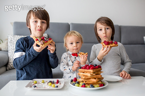 Sweet toddler birthday boy and his brothers, eating belgian waffle with raspberries, blueberries, cocnut and chocolate for breakfast