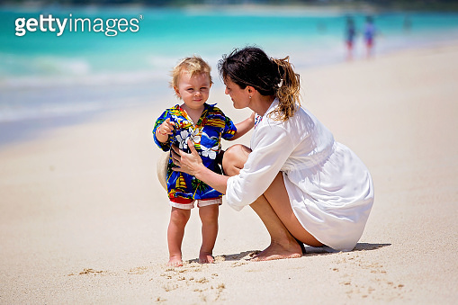 Mother and child playing at tropical beach. Family sea summer vacation. Mom and kid, toddler boy, play in the water. Ocean and water fun for parent and kids