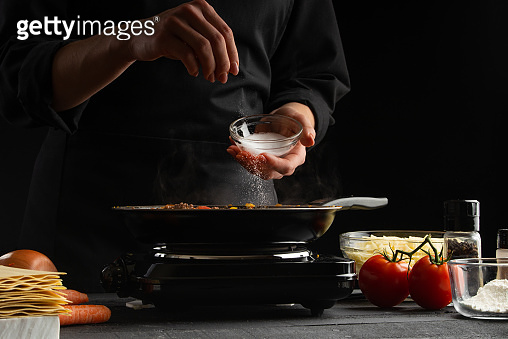 Chef cooks, fries in a pan. Cooking dishes. Ego salt. Freezing in motion.