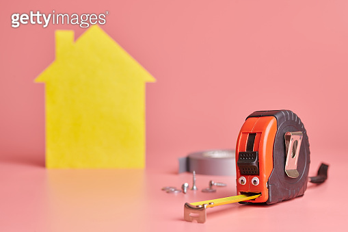 Metal tape measure funny concept. House renovation. Home repair and redecorated concept. Yellow house shaped figure on pink background.